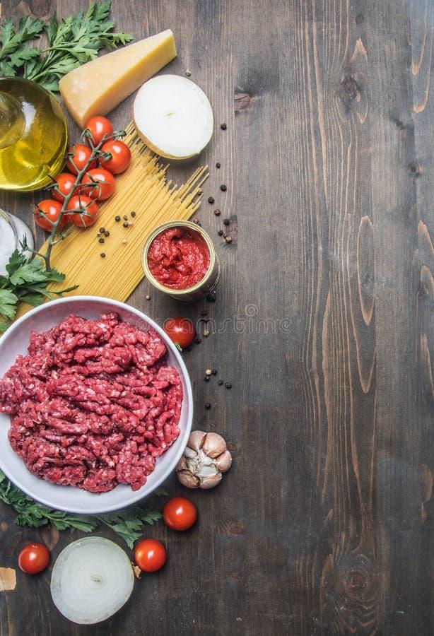 Bolognese deegwaren het koken concept, ruw gehakt, tomatenpuree, kersentomaten, deegwaren, ui, knoflook, kruidenkruiden, olie en  royalty-vrije stock fotografie
