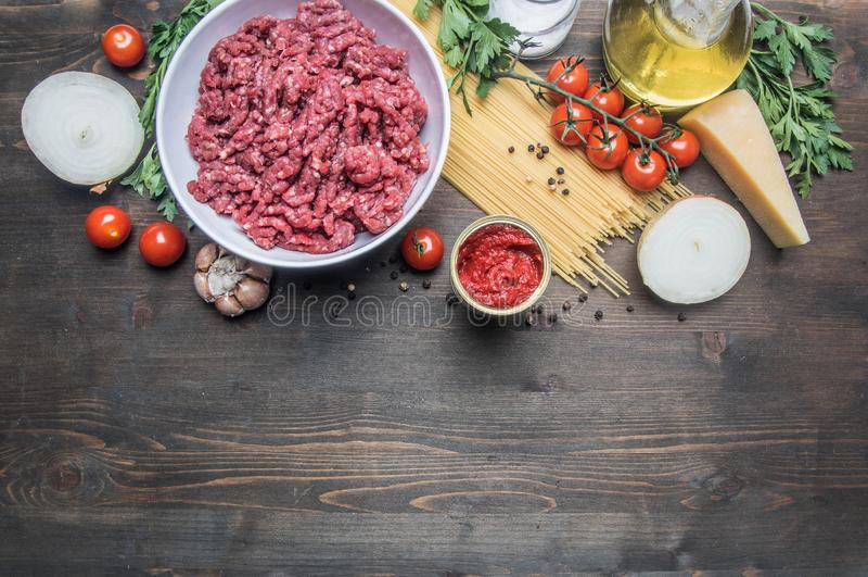 Bolognese deegwaren het koken concept, ruw gehakt, tomatenpuree, kersentomaten, deegwaren, ui, knoflook, kruidenkruiden, olie en  royalty-vrije stock afbeelding