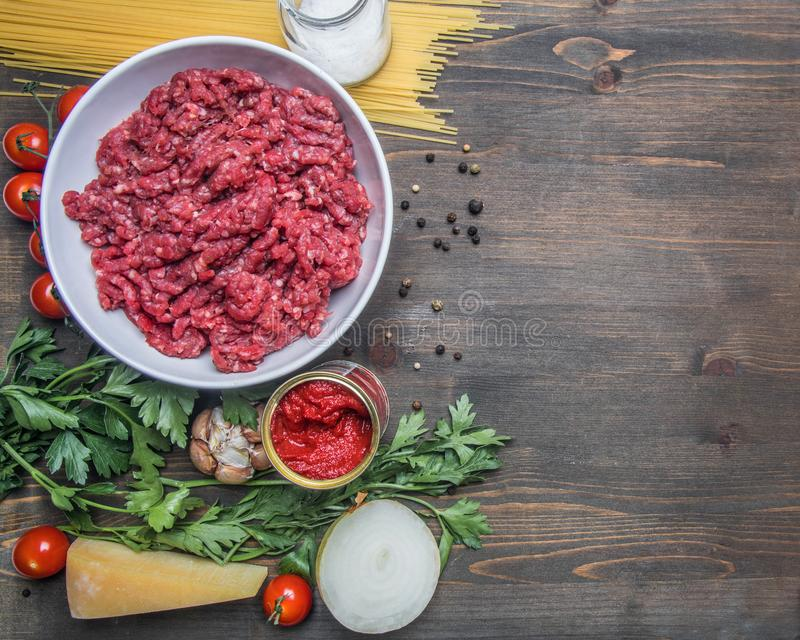 Bolognese pasta cooking concept, raw minced meat, tomato paste, cherry tomatoes, pasta, parmesan, onions, garlic, herbs herbs, stock photography