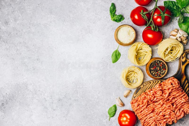 Bolognese pasta cooking concept: raw minced meat, tomatoes, pasta, parmesan, garlic, basil, olive oil stock photo
