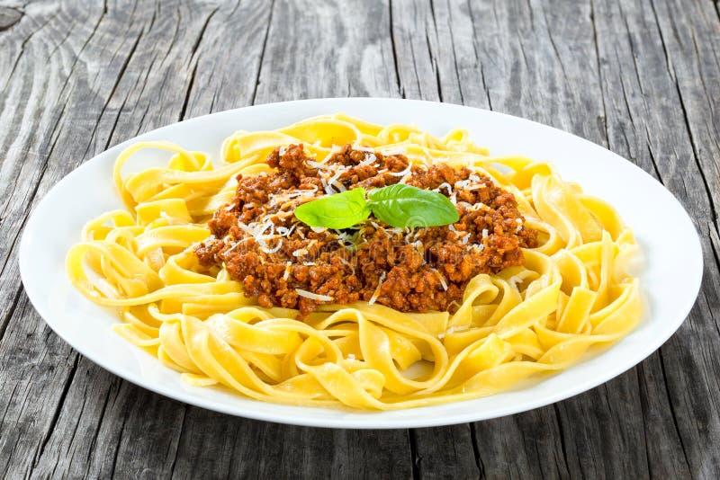 Bolognese ragu med italiensk pasta på en vit platta, närbild royaltyfria foton