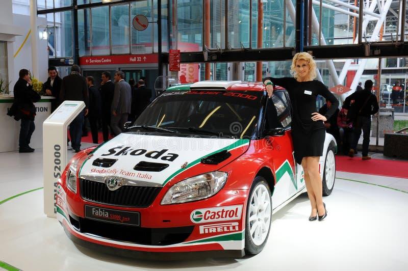 BOLONIA, ITALIA - 2 DE DICIEMBRE DE 2010: el modelo hermoso presenta con el coche de competición de Skoda en el salón del automóv foto de archivo