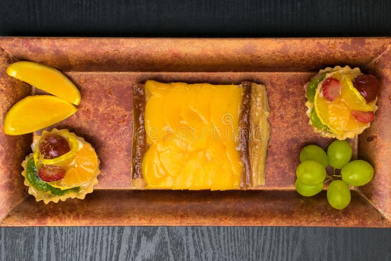 bolos caseiros frescos com fruto, abricó, uva, laranja, quivi na placa vermelha da decoração imagens de stock