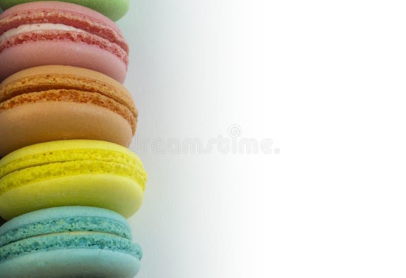 Bolos coloridos do macarrão lateralmente, em um fundo branco, rosa, laranja, amarelo, azul, espaço da cópia fotos de stock