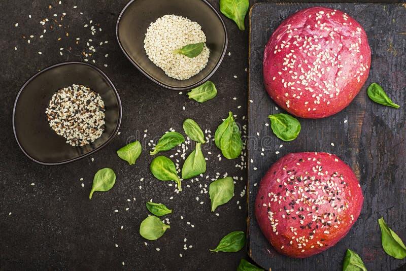 Bolos cor-de-rosa para o hamburguer vegetal com base na beterraba com as sementes de sésamo no fundo escuro Vista superior fotos de stock