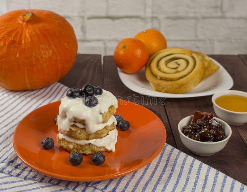 Bolos de queijo com creme de leite e mirtilos Panquecas do coalho com doce Café da manhã doce em cores mornas imagem de stock