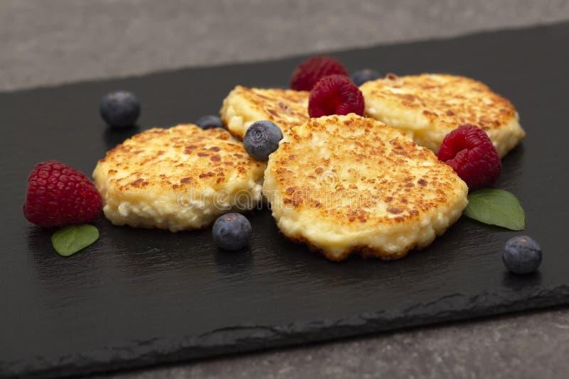 Bolos de queijo do requeij?o As panquecas do requeij?o ou os fritos do coalho decoraram framboesas e mirtilos frescos imagens de stock royalty free