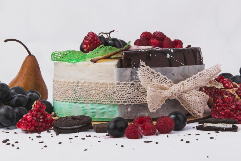 Bolos decorados com framboesas, peras, biscoitos, uvas, romã em um fundo branco foto de stock