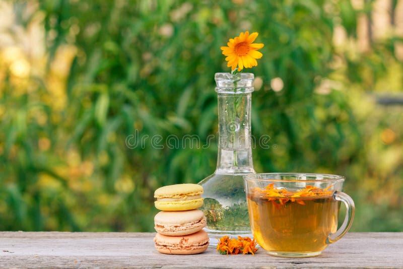 Bolos deliciosos dos bolinhos de am?ndoa da cor diferente, flor do calendula com uma haste em uma garrafa de vidro e copo do ch?  imagem de stock