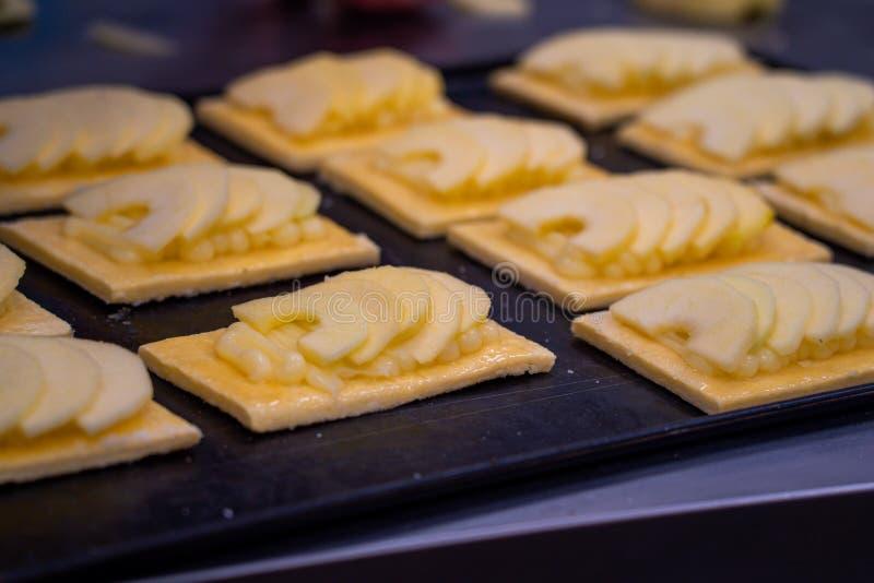 Bolos do artesão da torta de maçã em uma bandeja a ser cozida imagem de stock