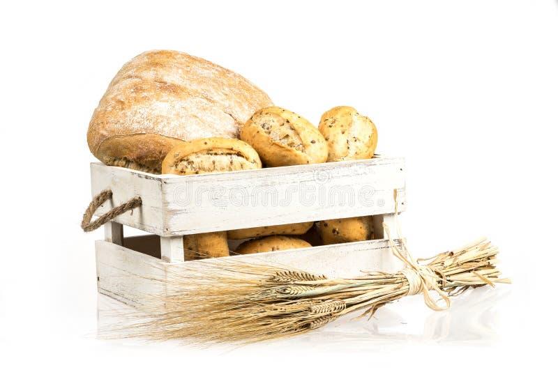 Bolos e ciabatta, pão na caixa de madeira Cevada e pães misturados frescos isolados no fundo branco foto de stock royalty free