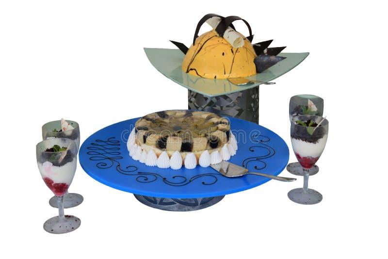 Bolos e pastelarias nos vidros com frutos, bagas e chocolate fotos de stock royalty free