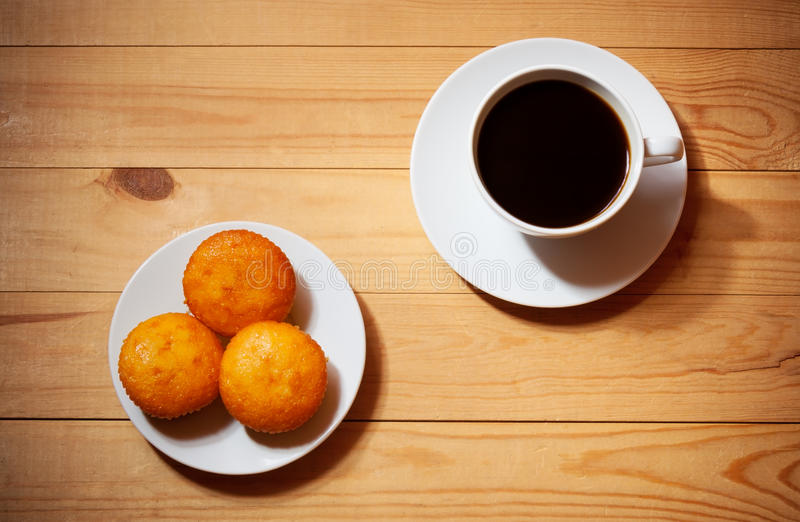 Bolos e xícara de café na tabela de madeira foto de stock royalty free