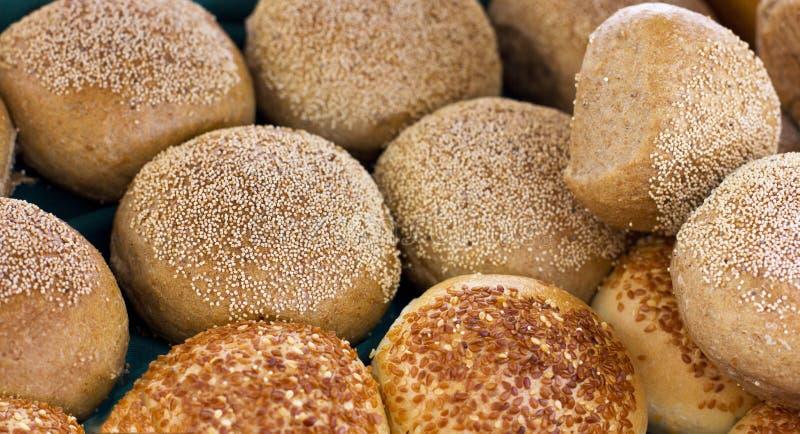 Bolos frescos da massa de fermento com as sementes do sésamo e de papoila imagem de stock