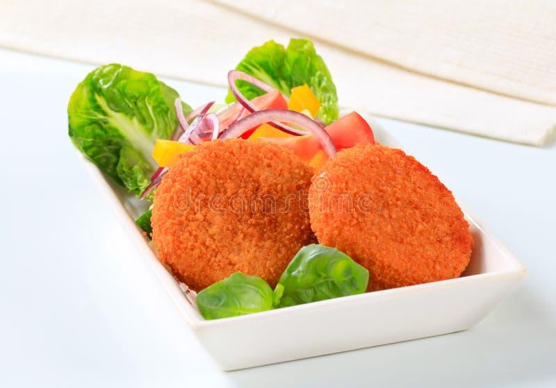 Bolos fritados do queijo ou de peixes com legumes frescos fotografia de stock royalty free