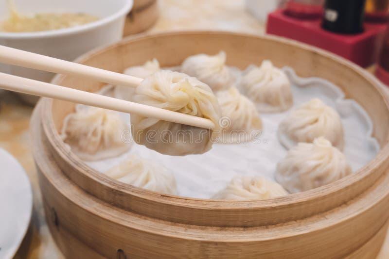 Bolos longos da bolinha de massa da sopa do bao de Xiao com os hashis no alimento chinês tradicional do restaurante em Taipei Tai imagem de stock