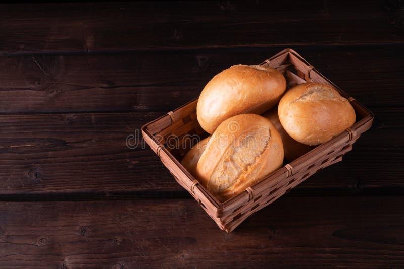 Bolos na cesta em um fundo de madeira, baixa chave do pão foto de stock