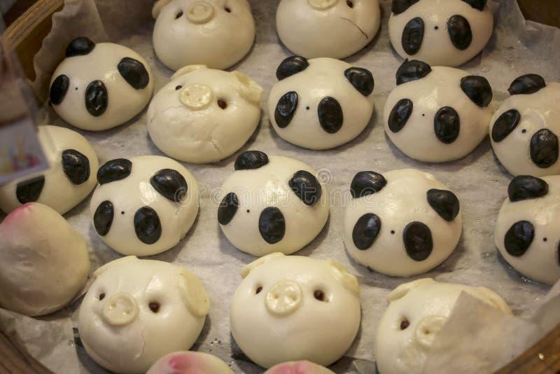 Bolos ou mantou cozinhado chinês feitos sob a forma das pandas e dos porcos dos animais foto de stock