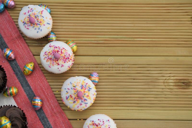 Bolos pequenos deliciosos com os ovos da páscoa do chocolate para a decoração e o espaço fotografia de stock