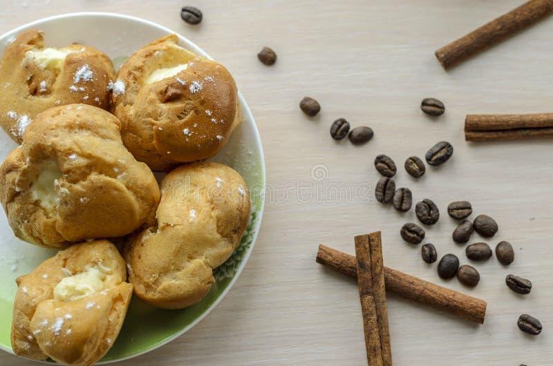 Bolos redondos com creme em uns pires com feijões de café, canela imagem de stock royalty free