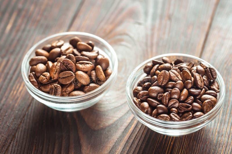 Bols d'arabica et de grains de café robusta photos stock