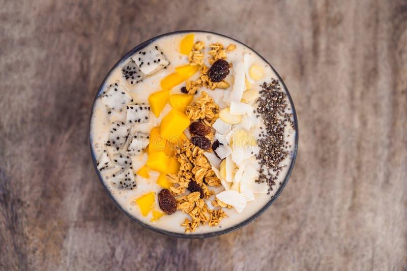 Bols de Smoothie faits avec la mangue, la banane, la granola, la noix de coco râpée, le fruit du dragon, les graines de chia et l image stock