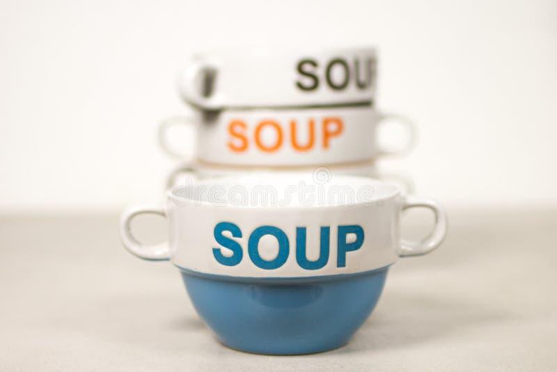 Bols de soupe en céramique empilés avec la SOUPE à Word sur eux bleus dans l'avant photos stock