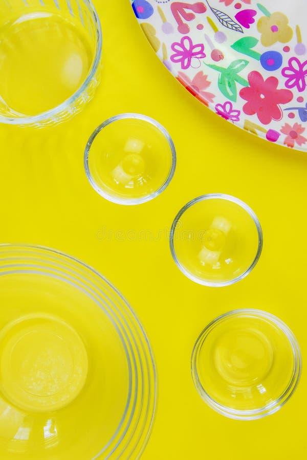 Bols en verre et plat brillamment coloré sur le fond jaune image stock