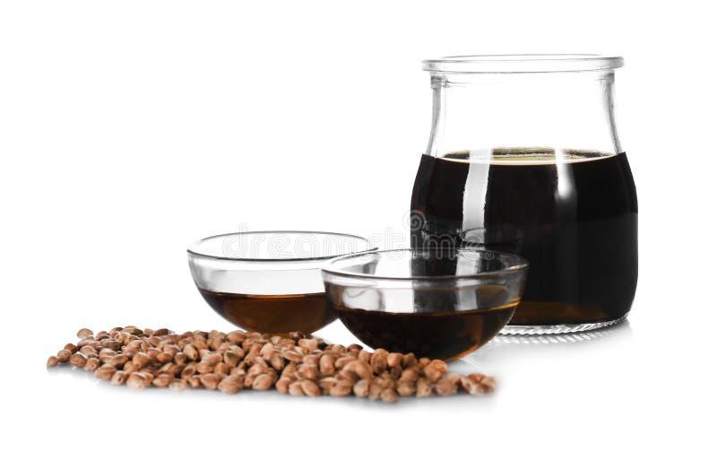 Bols en verre et pot avec de l'huile de chanvre photographie stock libre de droits