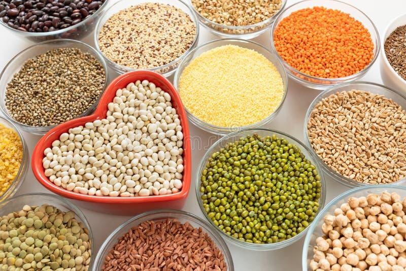 Bols en verre en gros plan avec des céréales, des haricots et des graines avec la cuvette en forme de coeur rouge au milieu sur l photographie stock libre de droits