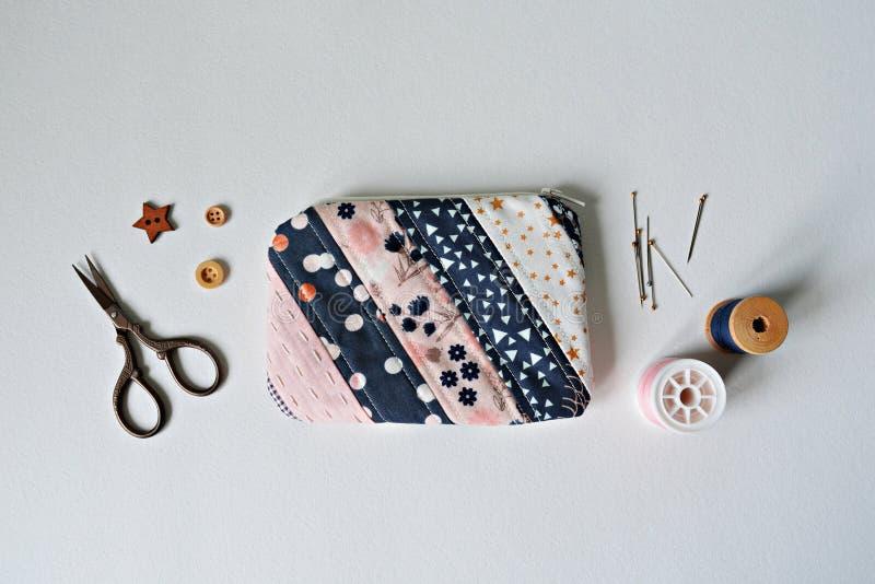 Bolsa acolchada de la noción del remiendo, hilo, pernos de metal, tijeras y botones de madera foto de archivo