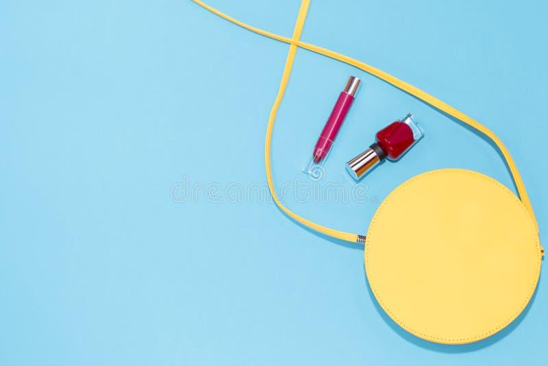 Bolsa amarela redonda, verniz para as unhas vermelho, batom vermelho em um fundo azul pastel imagem de stock royalty free