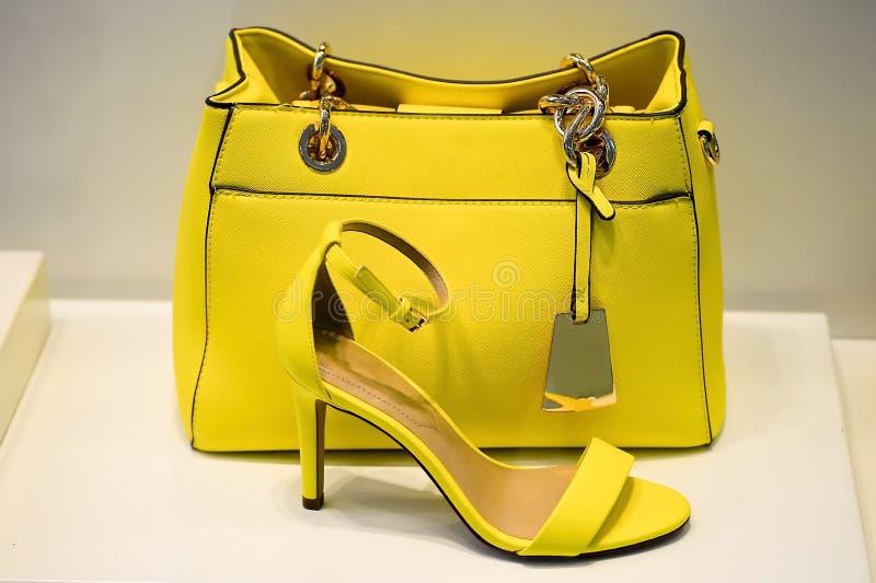 Bolsa amarilla con un tono verdoso en zapatos combinados los mismos colores. El estilo y el gusto imagen de archivo