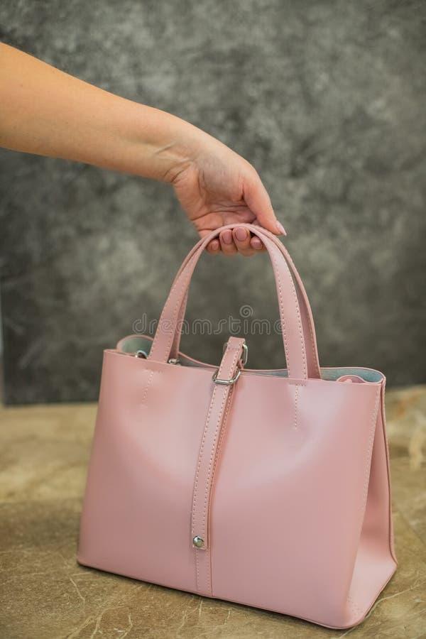 Bolsa cor-de-rosa do saco de couro da forma à moda da posse da mão da mulher isolada no fundo cinzento Mulher elegante Forma fotografia de stock