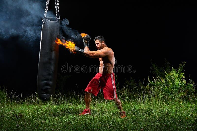Bolsa de arena de perforación del boxeador profesional al aire libre con su glo del boxeo imágenes de archivo libres de regalías