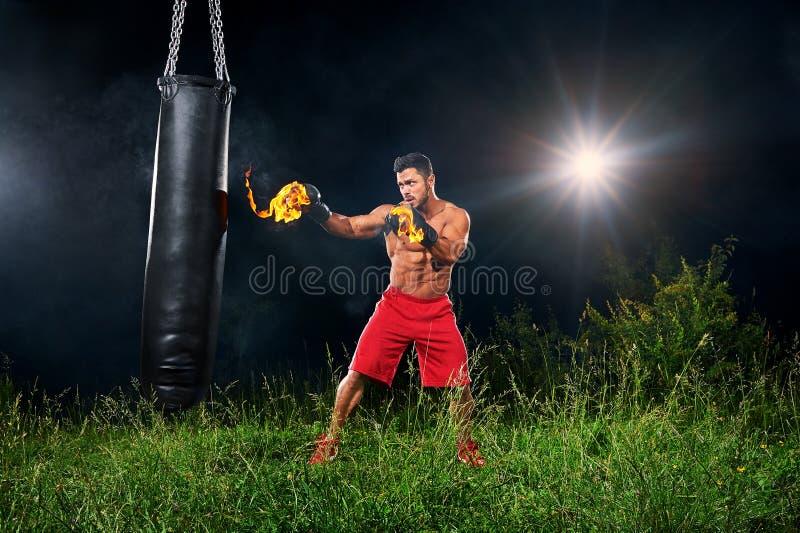 Bolsa de arena de perforación del boxeador profesional al aire libre con su glo del boxeo imagenes de archivo