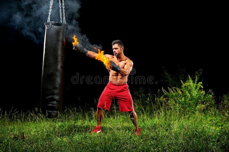 Bolsa de arena de perforación del boxeador profesional al aire libre con su glo del boxeo foto de archivo