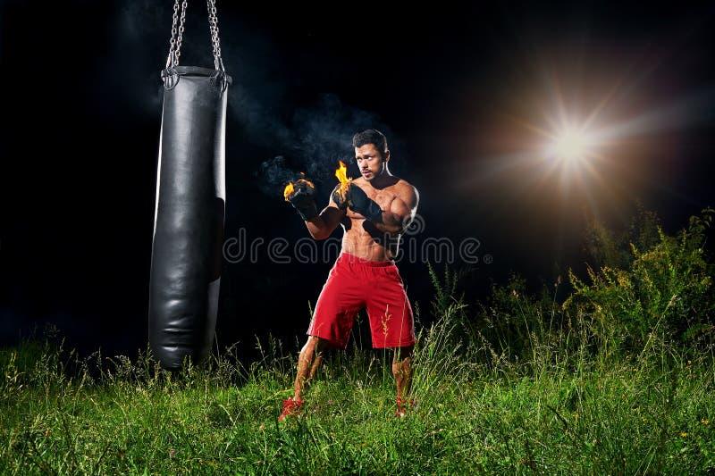 Bolsa de arena de perforación del boxeador profesional al aire libre con su glo del boxeo fotos de archivo libres de regalías