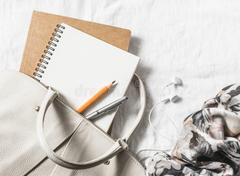 A bolsa de couro das mulheres, bloco de notas vazio limpo, pena e lenço em um fundo claro, vista superior Espaço livre foto de stock royalty free