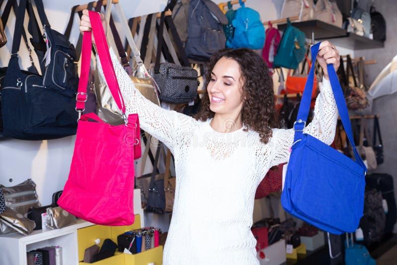 Bolsa de couro de compra da jovem mulher na loja das miudezas imagem de stock royalty free