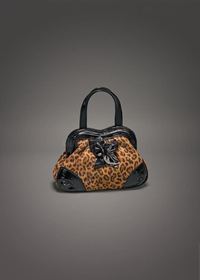 Bolsa de couro pequena com teste padrão do leopardo no fundo cinzento do inclinação imagens de stock royalty free