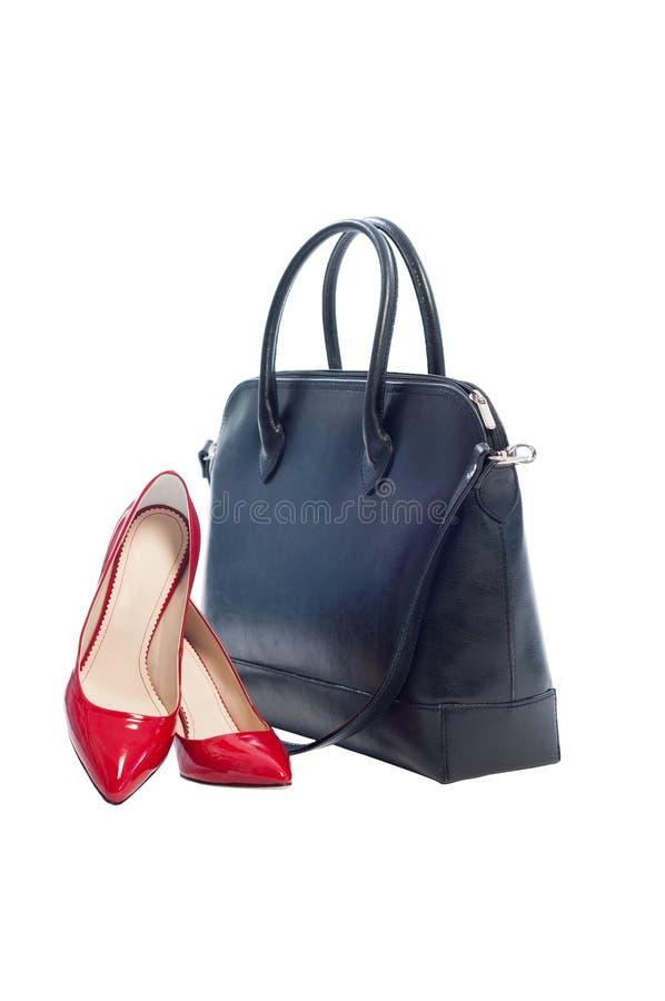 Bolsa de couro preta e pares de sapatas do vermelho da mulher imagens de stock
