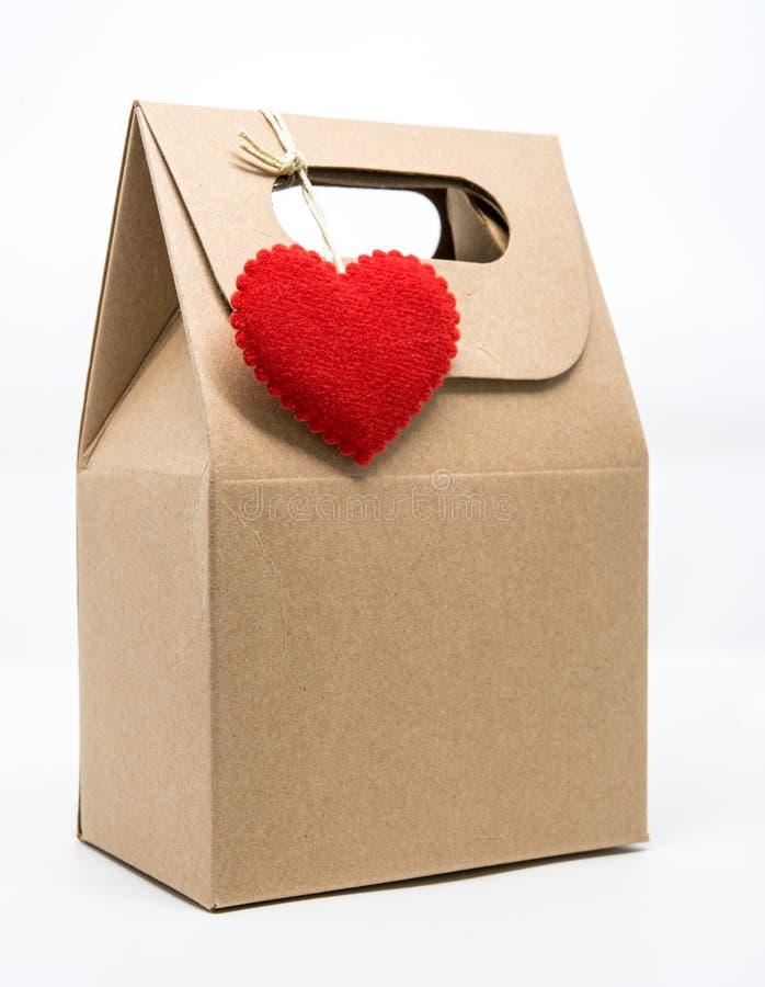 Bolsa de papel con el corazón rojo sobre el documento de embalaje sobre el fondo blanco imagenes de archivo