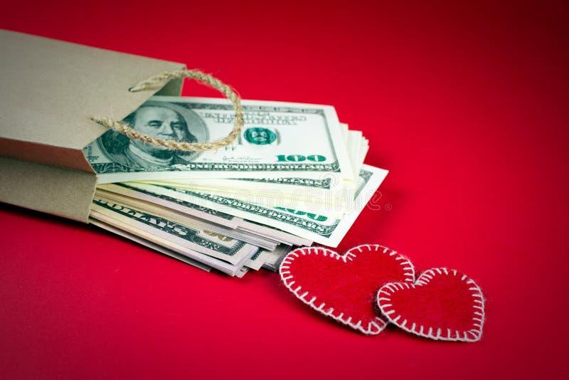 Bolsa de papel con el día de tarjeta del día de San Valentín decorativo del St de los corazones del dinero fotos de archivo