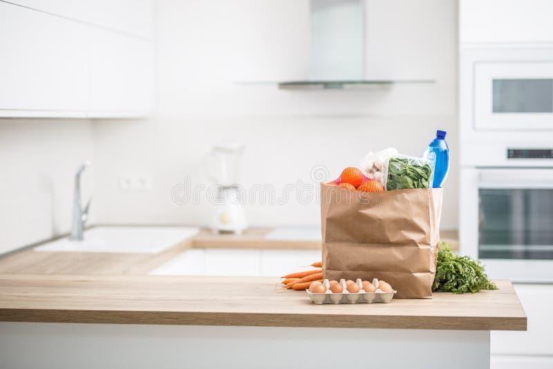 Bolsa de papel con la compra en la cocina casera fotografía de archivo