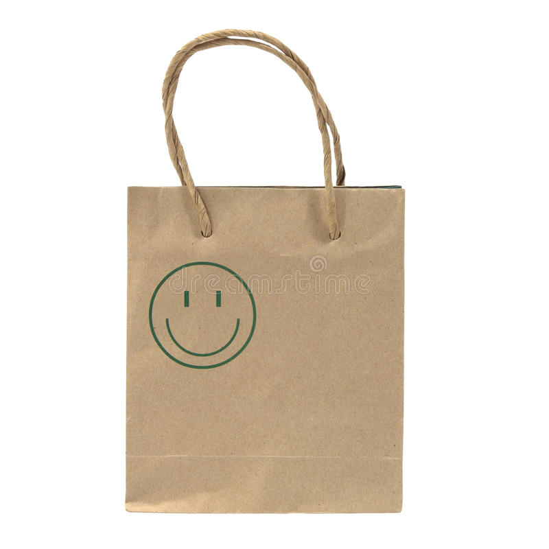 Bolsa de papel de Brown con la cara verde de la sonrisa aislada en blanco imagen de archivo libre de regalías