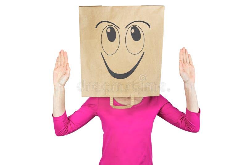 Bolsa de papel de la mujer que lleva con la expresión facial feliz en la cabeza fotografía de archivo