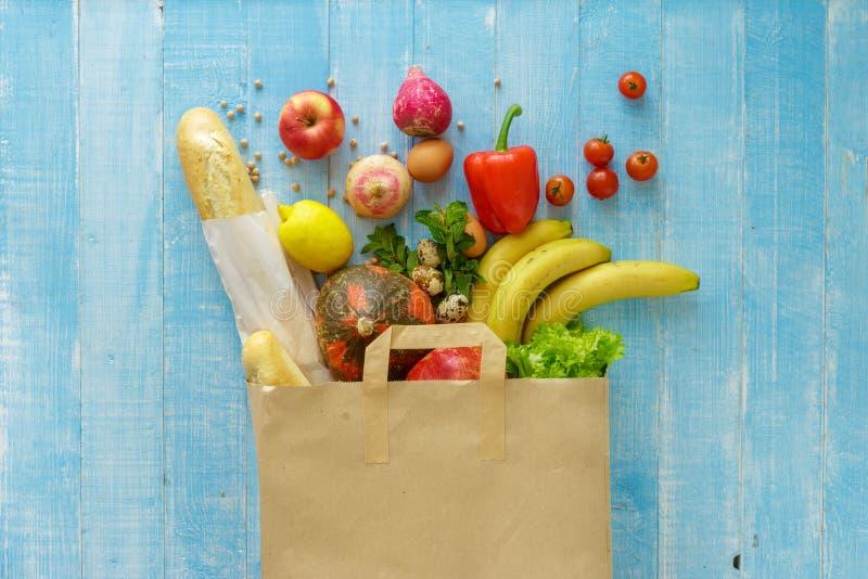 Bolsa de papel de diversa comida sana en fondo de madera azul foto de archivo