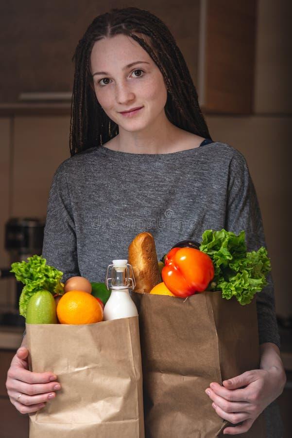 Bolsa de papel llena de la tenencia de la mujer con los productos en manos en el fondo de la cocina Alimento biológico sano y fr fotografía de archivo