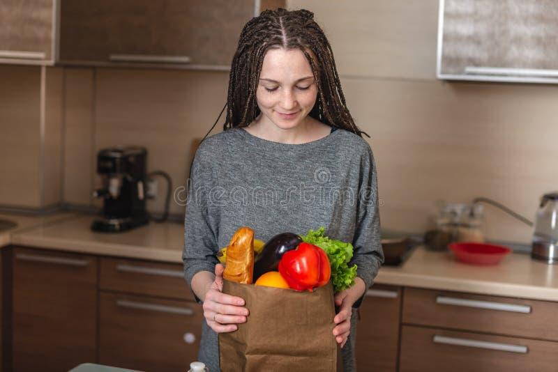 Bolsa de papel llena de la tenencia de la mujer con los productos en manos en el fondo de la cocina Alimento biológico sano y fr imagen de archivo libre de regalías